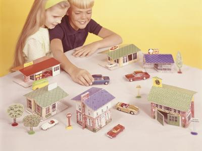 Boy and Girl (8-9) Playing With Doll Houses and Cars, Elevated View