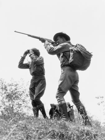 Couple in Brush, Man Aiming Hunting Rifle, Woman Standing Looking Through Binoculars
