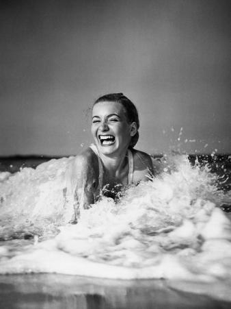 Young Woman Lying in Surf, Laughing