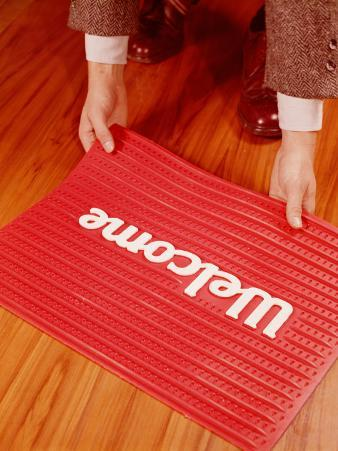 Man's Hands Laying Down Welcome Mat