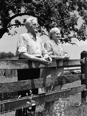 Elderly Couple on Farm Standing at Wooden Fence Looking Off Into Distance