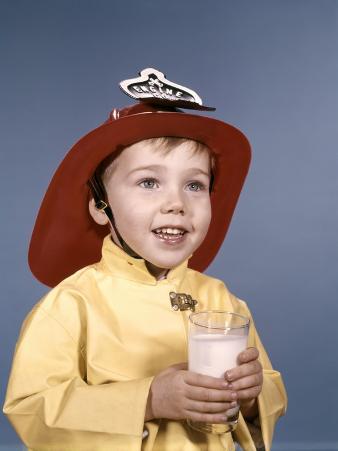 Boy in Fireman Costume Holding Glass of Milk