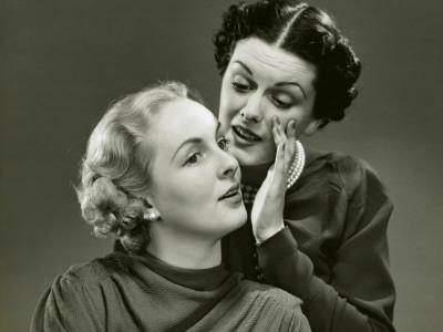 Woman Gossips Into Another's Ear