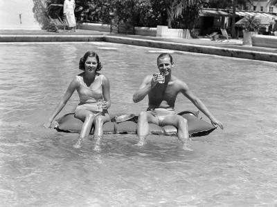 Couple Sitting on a Float in a Swimming Pool
