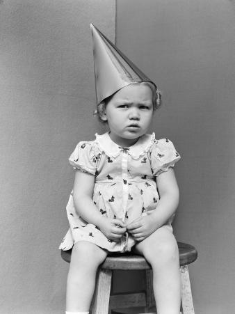 Girl Wearing Dunce Cap Sitting on Stool in Corner