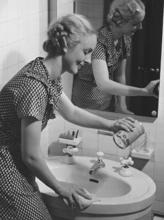 Young Woman Cleaning Bathroom Sink