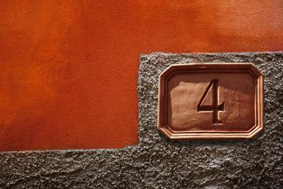 Number 4 Sign against a Painted Plaster Wall
