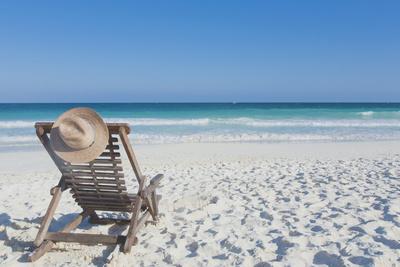 Beach Chair with a Hat, on an Empty Beach