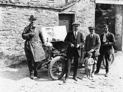 Bedford Standing at the Front of a Car, with Onlookers