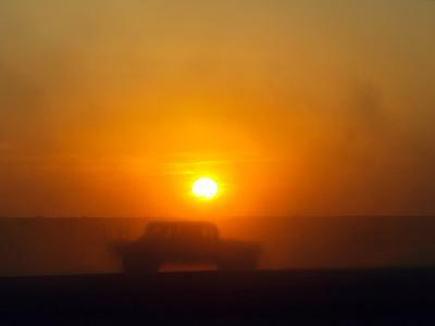 An American Humvee Drives Through the Desert at Sunset Near the Iraqi Border