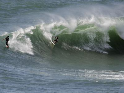 Surfers Ride a Large Wave of Sydney's Manly Beach
