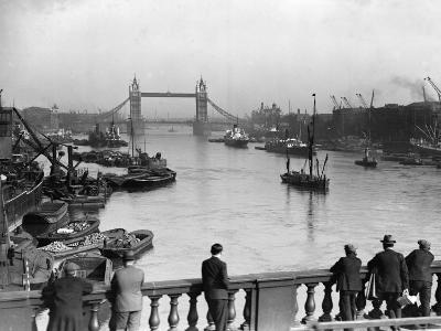 Pedestrians on London Bridge Watch Boats and Barges Being Unloaded