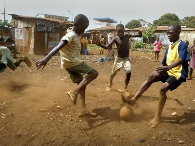 Young Children Play Soccer on a Dirt Pitch by the Side of Railway Tracks
