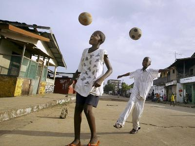 Children Play Soccer on a Street