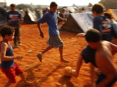 Children Play Soccer Between Tents Placed on a Dusty Lot
