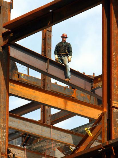 A Construction Worker Stands On A Steel Beam While Working