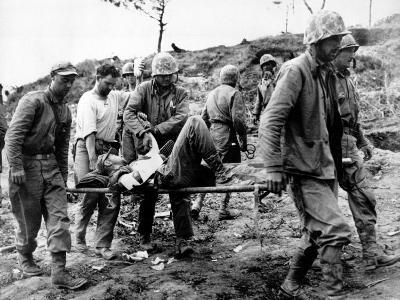 A U.S. Navy Corpsman Administers Blood Plasma to a Wounded Marine