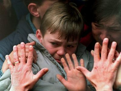 A Father's Hands Press against the Window of a Bus Carrying His Tearful Son and Wife to Safety