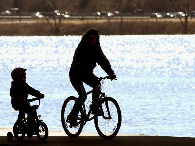 A Mother and Son are Silhouetted as They Ride Along the Schuylkill River