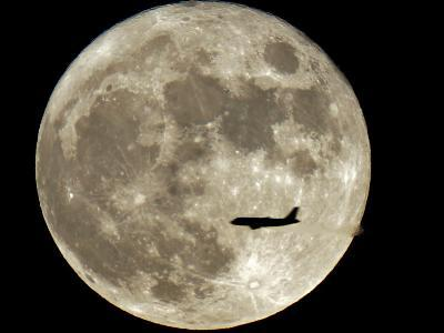 Jet is Silhouetted on the Full Moon in St. Petersburg, Russia