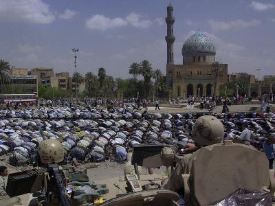 A Crowd of Iraqi Protesters Pray in Front of a U.S. Military Checkpoint