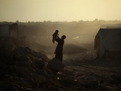 Displaced Man Holds His Baby Next to His Tent in Jalozai Refugee Camp Near Peshawar, Pakistan