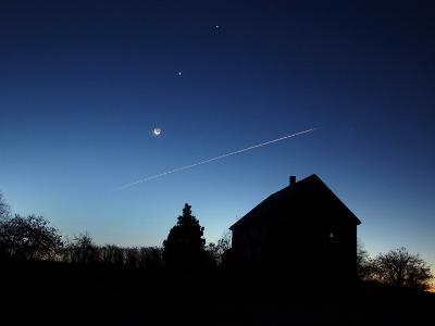 Crescent Moon, and the Planets Venus and Jupiter In a Rare Alignment, Shine Above a Farmhouse