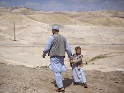 Palestinian Father and Son Walk in Desert During Celebrations Marking the Annual Day of Nebi Musa