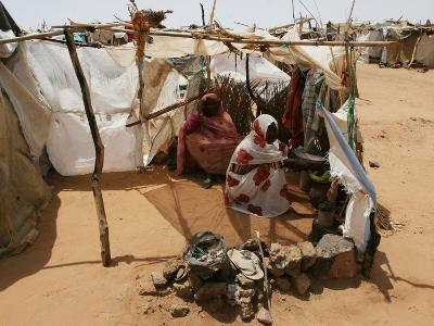 Two Sudanese Women Sit at a Make Shift Hut