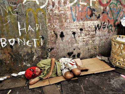 An Indonesian Boy Wearing a Spiderman Mask Sleeps on a Piece of Cardboard