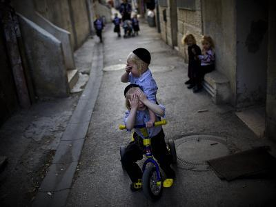 Ultra-Orthodox Jewish Children Cover their Faces as They Play in a Street in Jerusalem