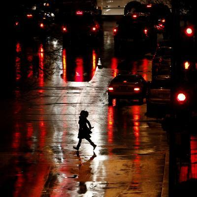 Pedestrian in Rain-Soaked Street in Country Club Plaza Shopping District of Kansas City, Missouri
