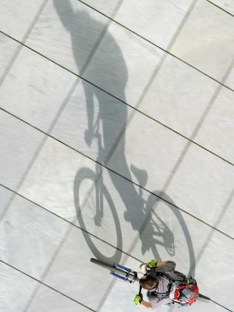 Sun Casts the Shadow of a Cyclist in Berlin, Germany