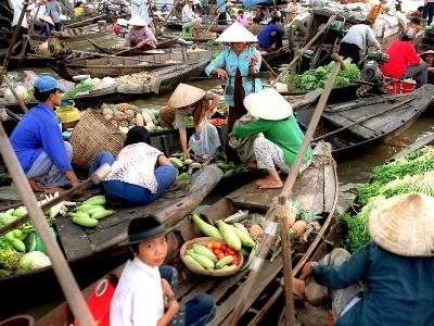 Small Wooden Boats Loaded with Fresh Produce Gather Along a Canal