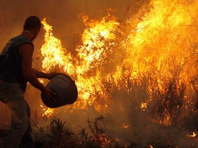 A Local Resident Throws a Bucket of Water on a Forest Fire