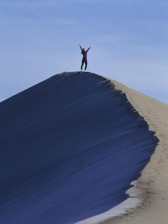 Woman Exercising on the Top of a Sand Dune