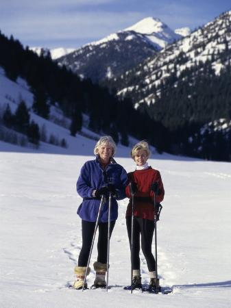 Portrait of a Senior Woman and a Young Woman Standing Wearing Skis