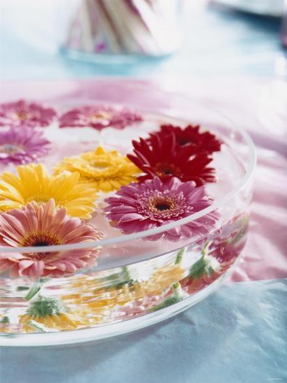 A Bowl Of Flowers Floating In Water Table Decoration
