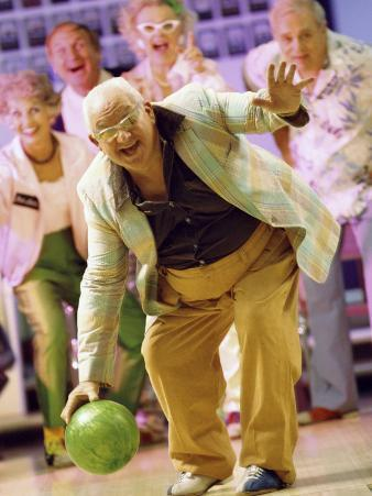 People Watching a Senior Man Bowling at a Bowling Alley