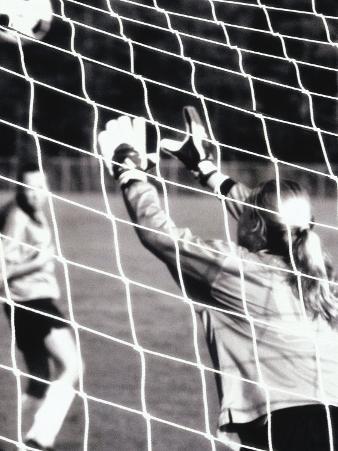 Female Goalie Attempting to Stop a Soccer Ball