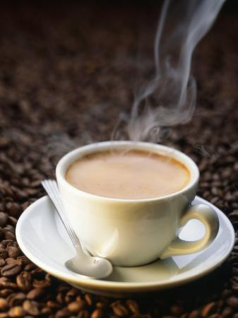 A Steaming Cup of Coffee on Coffee Beans