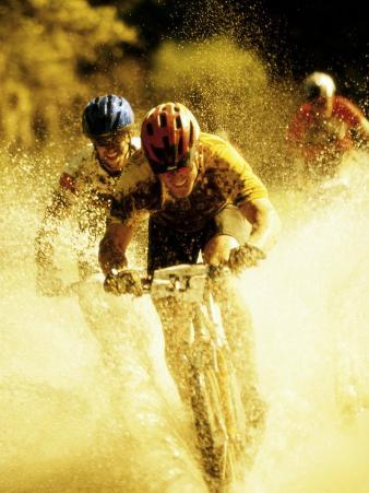 Young Men Riding Bicycles Through Water