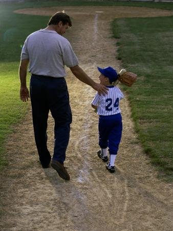 Rear View of a Man Walking with His Son at a Playing Field