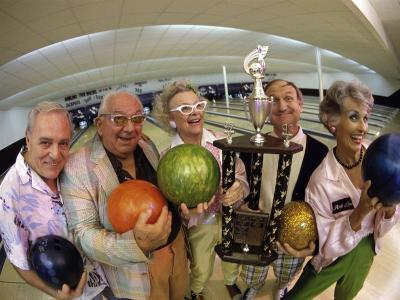Portrait of a Group of Senior People Holding a Bowling Trophy at a Bowling Alley
