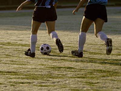 Low Section View of Two Female Soccer Players Kicking a Soccer Ball