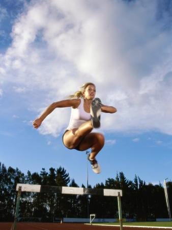 Low Angle View of a Female Athlete Jumping Over a Hurdle