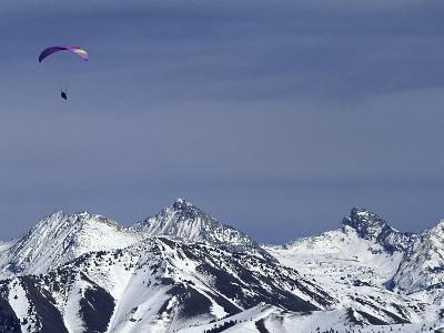 Paraglider Over Snowy Mountains