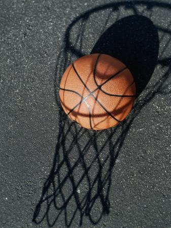 Close-up of a Basketball Resting on The Shadow of a Basketball Hoop