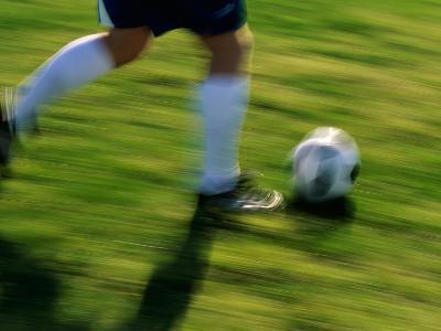 Low Section View of a Soccer Player Running with The Ball