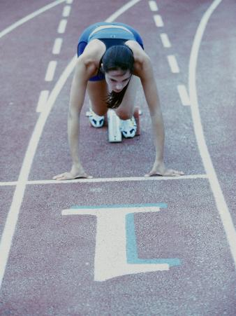 High Angle View of a Young Woman at The Starting Position of a Running Track